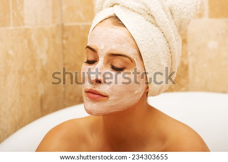 Portrait of relaxing woman with closed eyes and cream lotion on face - stock photo