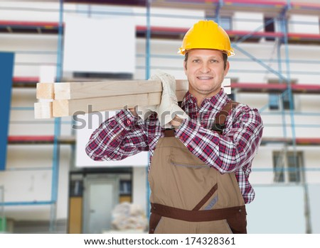 Portrait Of Repairman Carrying Plank Of Wood - stock photo