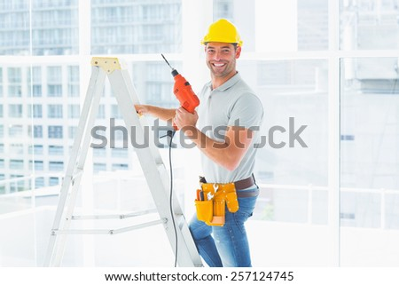 Portrait of repairman with drill machine climbing ladder in building - stock photo