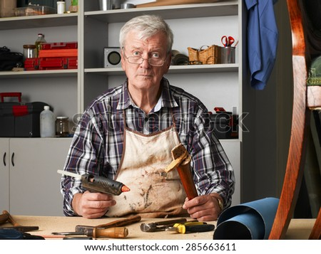 Portrait of retired carpenter sitting at his workshop and repair the broken legged chair. Small business. - stock photo