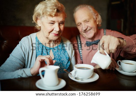 Portrait of retired couple in smart clothes having tea in cafe - stock photo