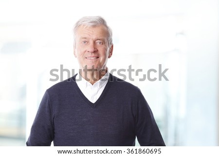 Portrait of retired professional man standing at office while looking at camera and smiling.  - stock photo