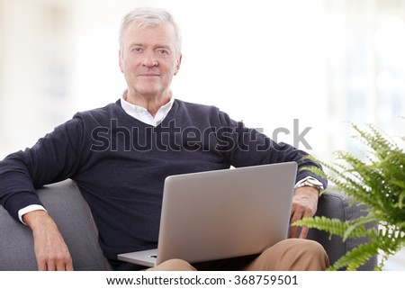 Portrait of retired senior man sitting at home and working online with laptop.  - stock photo