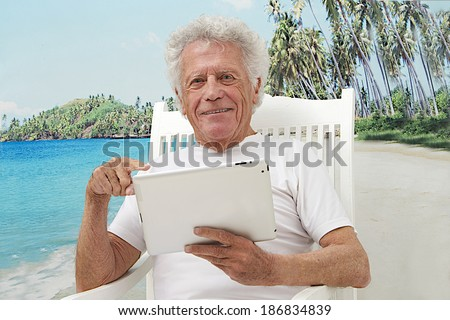 portrait of retirement senior man  seated in summer with, tropical beach background using tablet computer   - stock photo
