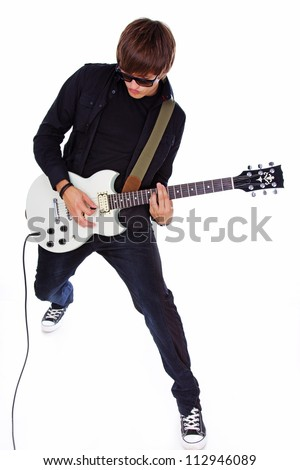 Portrait of rock artist posing in studio with guitar in glasses