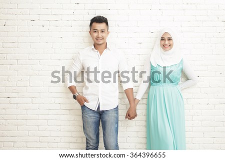 portrait of romantic asian couple standing and smiling while holding each other hands - stock photo