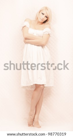 Portrait of romantic blond woman in long white dress - stock photo