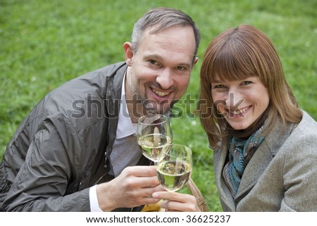portrait of romantic couple drinking champagne in a park