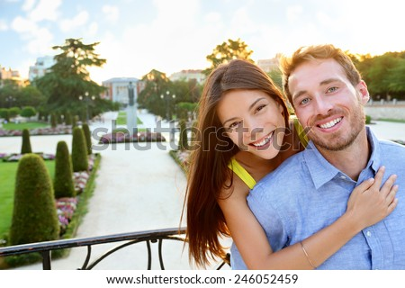 Portrait of Romantic couple embracing in love looking at camera. Multicultural man and woman smiling happy in el Retiro in Madrid, Spain, Europe. Asian girl, young Caucasian man. - stock photo