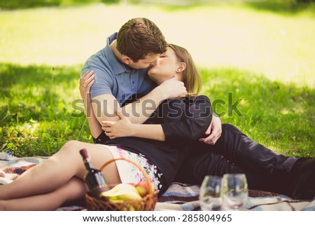 Portrait of romantic couple kissing on blanket at park - stock photo