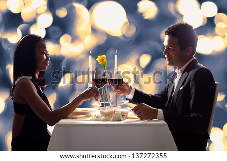 Portrait Of Romantic Couple Toasting Red Wine At Dinner - stock photo