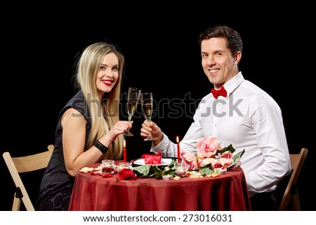 Portrait Of Romantic Couple Toasting white Wine At Dinner  on black background - stock photo