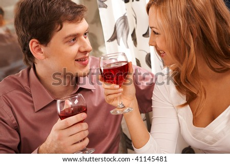 Portrait of romantic couple with wineglasses looking at each other - stock photo