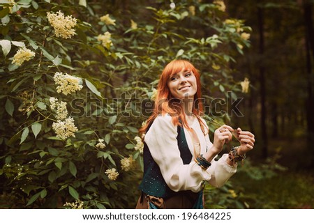 Portrait of romantic hippie woman smile in the woods. Young girl with hippie dress walking in the forest. Redhead girl in boho style. - stock photo
