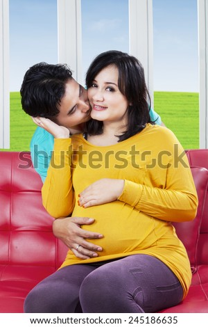 Portrait of romantic husband kissing his pregnant wife cheek at home - stock photo