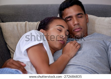 portrait of romantic married couple sleeping on sofa couch in home living room - stock photo