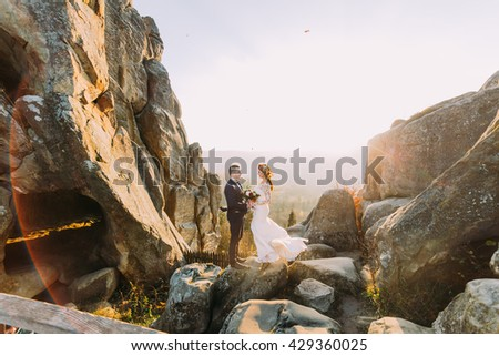 Portrait of romantic newlywed couple in sunset lights on majestic mountain landscape with big rocks as backround
