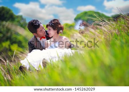 Portrait of romantic teenage couple sitting in green grass - stock photo