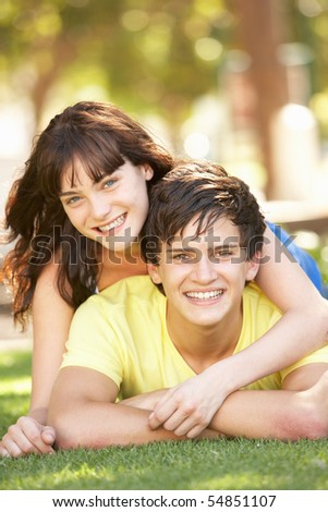 Portrait Of  Romantic Teenage Couple Sitting In Park - stock photo