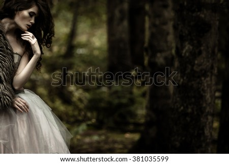 Portrait of romantic woman in beautiful dress in fairy forest - stock photo