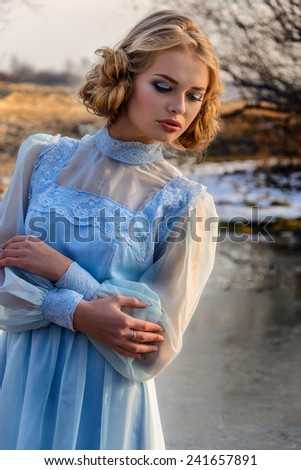 Portrait of romantic woman in vintage dress on the river bank