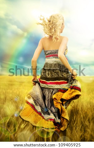 Portrait of romantic woman running across field from behind - stock photo