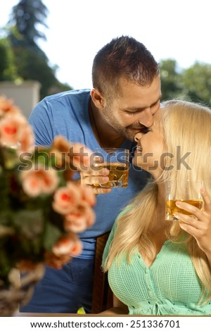 Portrait of romantic young couple kissing with drinks in hand, outdoors. Attractive, busty blonde woman with cleavage. - stock photo
