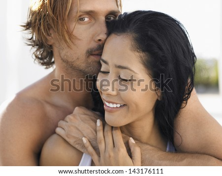 Portrait of romantic young man embracing woman from behind - stock photo