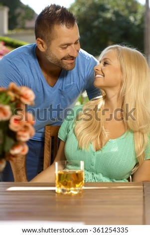 Portrait of romantic young married couple, summer, outdoors. Attractive, busty blonde woman with cleavage. Looking at each other. - stock photo