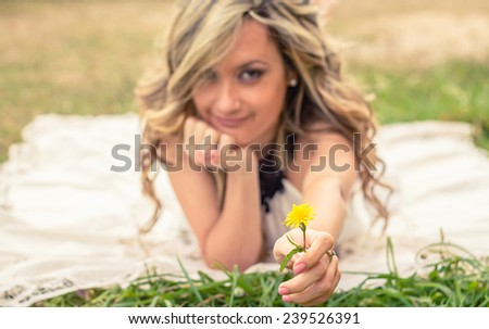 Portrait of romantic young woman showing a yellow flower in her hand lying down over the grass. Selective focus in the flower. - stock photo