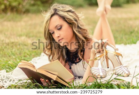 Portrait of romantic young woman with her shoes in the hand reading a book lying down over the grass. Selective focus on the shoes. - stock photo