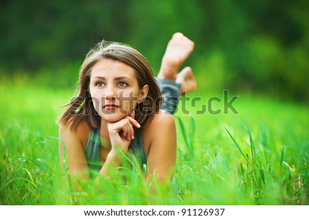 portrait of romantic, young woman with short hair lying on green grass (meadow, prairie) barefoot, dreams - stock photo