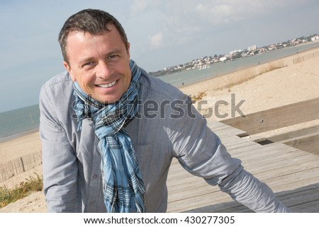 Portrait of rugged middle aged man standing at the beach