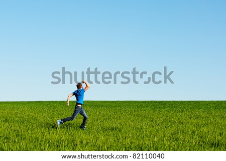 portrait of running man on green field - stock photo