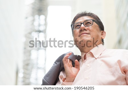 Portrait of 60s Asian Chinese CEO boss smiling and looking away. Senior male businessman, real modern office building as background. - stock photo
