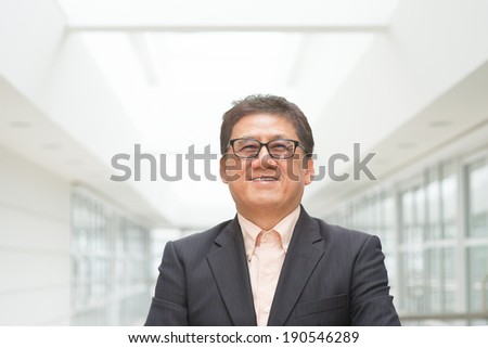 Portrait of 60s Asian Chinese CEO boss smiling. Senior male businessman, real modern office building as background. - stock photo