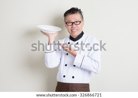 Portrait of 50s mature Asian male chef in uniform presenting dish and smiling, empty plate ready for food, standing on plain background with shadow, copy space. - stock photo