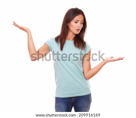 Portrait of 30s pensive female on blue jeans holding her palms up while standing on isolated white background - copyspace - stock photo