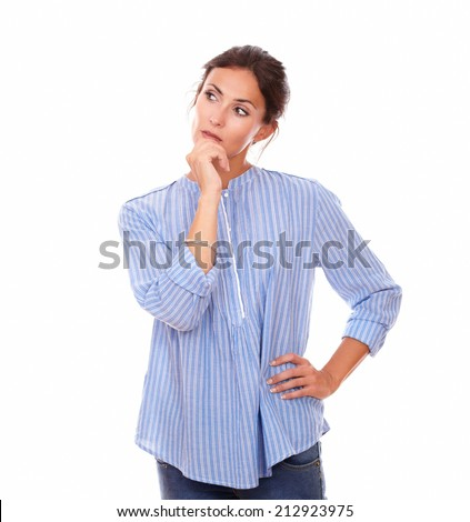 Portrait of 30s pretty woman on blue shirt looking right and wondering while standing on isolated white background - copyspace - stock photo