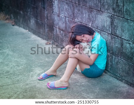 portrait of sad and lovely Asian girl against grunge wall background  - stock photo