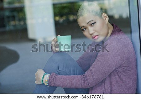 Portrait of sad Asian with a cup of tea sitting at window - stock photo