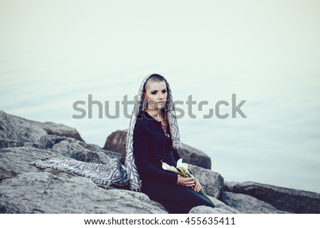 Portrait of sad beautiful Caucasian white young bald woman with shaved hair head covered with scarf shawl looking away, sitting by water on rocks holding lily flowers, toned with Instagram filters  - stock photo
