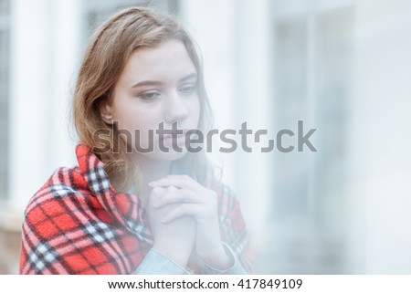Portrait of sad beautiful young woman. She wrapped herself in a blanket - stock photo