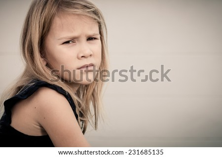 Portrait of sad blond little girl sitting near wall on outdoors - stock photo