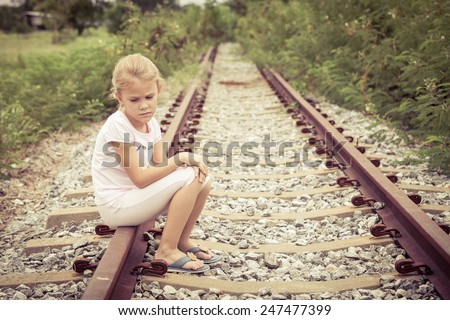 Portrait of sad blond little girl sitting on the rails at the day time - stock photo