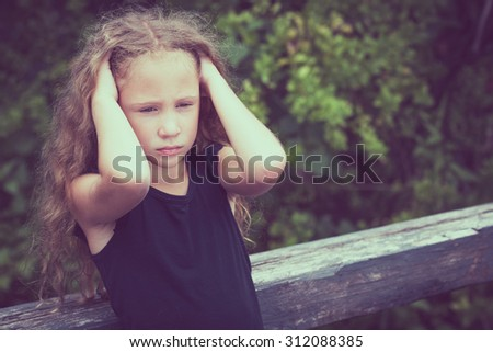 Portrait of sad blond teen girl standing on the bridge at the day time - stock photo