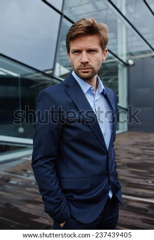 Portrait of sad businessman standing with hands in suit pockets, desperate businessman standing against skyscraper office building, portrait of defeat businessman looking away