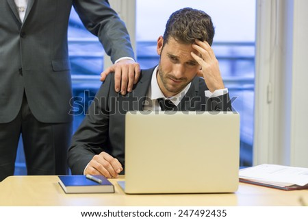 Portrait of sad businessman with her boss at background. Hand on shoulder - stock photo