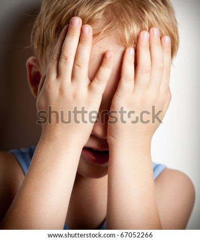 Portrait of sad crying little boy covers his face with hands - stock photo