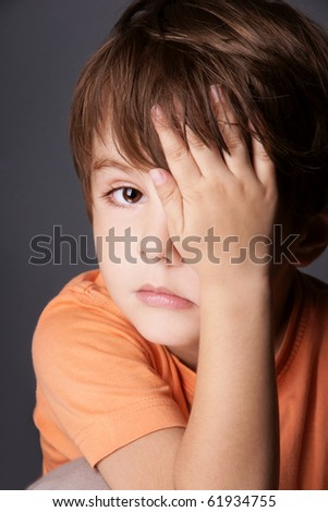 Portrait of sad cute little boy closed one eye with his hand, studio shot - stock photo